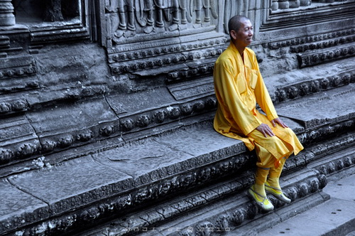 Angkor Wat was built as a Hindu temple honoring Vishnu between 1,115-1,150 AD. Cambodia adopted Buddhism in the 13th century and Buddhist monks have maintained the temple since that time.  Angkor Wat monk. © Copyright Gary Ng.
